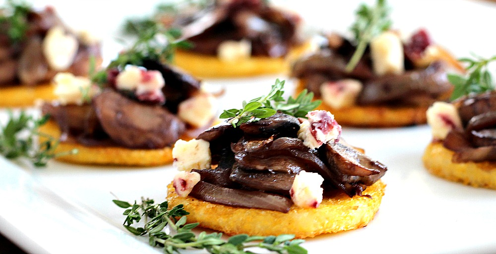Caramelized Mushroom Polenta Bites. Crispy baked polenta rounds topped with caramelized onions and mushrooms sauteed with cabernet, white stilton cranberry cheese and garnished with thyme. Gluten free, vegetarian with vegan option. Perfect for holiday and New Year's Eve parties.