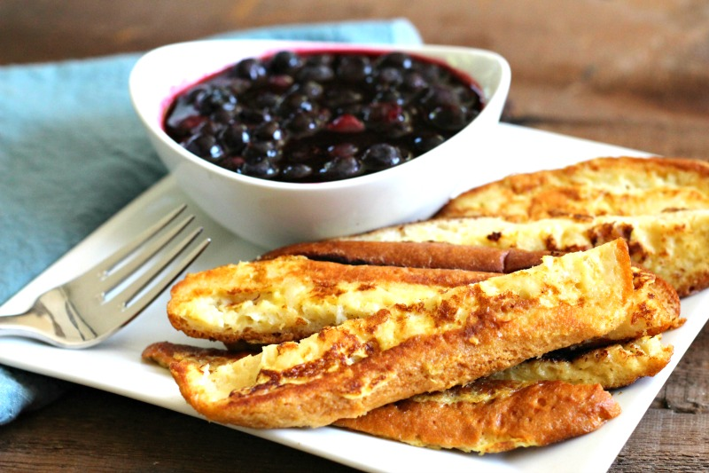 Gluten Free French Toast Sticks with low sugar Blueberry Sauce . Made with Canyon Bakehouse hot dog buns these French toast sticks are allergy friendly and easy to make!